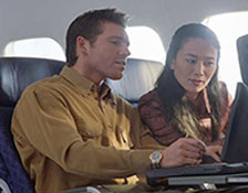 Image shows a traveler is using his laptop in the airplane